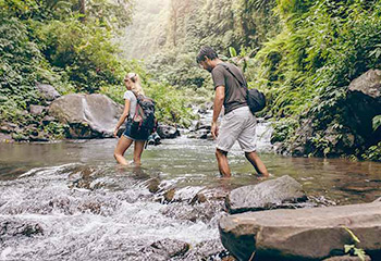 Couple Bushwalking in the Rainforest through a cooling stream